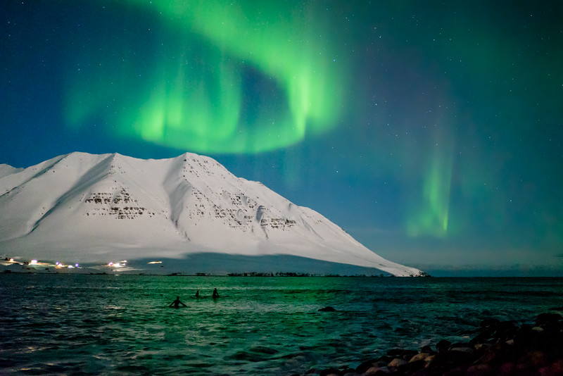 Surfers under the Northern Lights