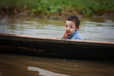 A young Burmese boy riding on a boat with his dad through the floating villages. Inle Lake, Myanmar