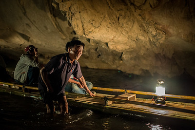 A Thai local guides a bamboo raft through a cave near Pai, Thailand