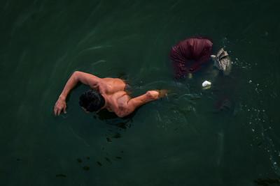 A Burmese fisherman carries his gear through the lake in Mandalay, Myanmar