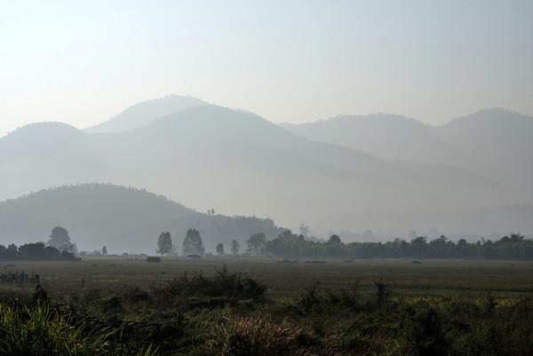 Glimpse of a nearby mountain range while riding a motorbike through Lamphun