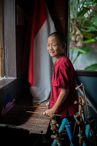 Student playing a traditional Thai instrument