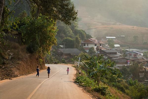 Children running toward a village in the mountains of Mae Rim, Thailand