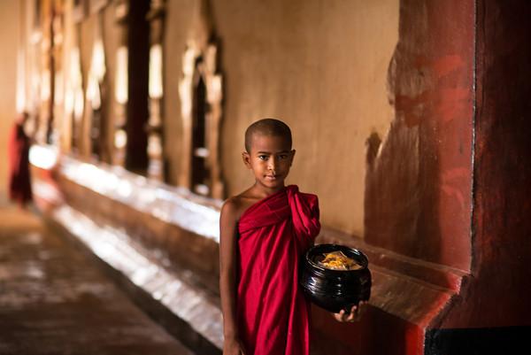 Young Burmese monk walking through a temple in Old Bagan, Myanmar