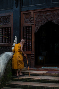 Thai monk, removing his shoes before entering the temple