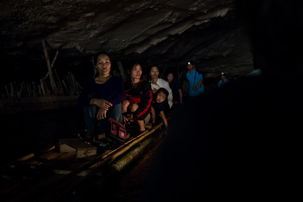 A Thai family floats through a cave on a bamboo raft near the town of Pai, Thailand