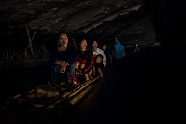 A Thai family floats through a cave on a bamboo raft near the town of Pai, Thailand