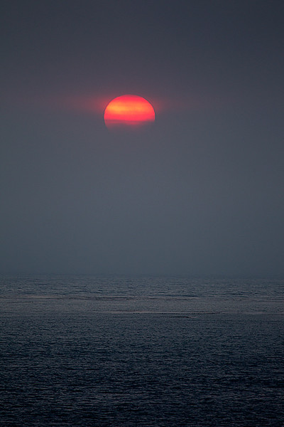 Sun Partially Obscurded by Fog Over Ocean