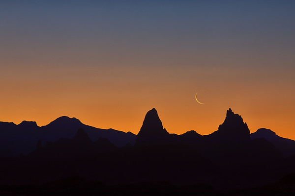 Crescent Moon rising between the Mule Ears at dawn, Big Bend National Park, Texas