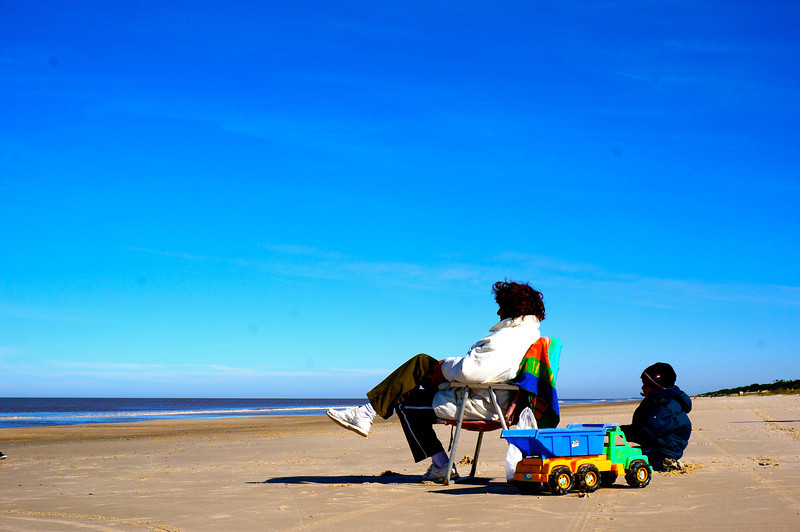 A woman and her son sit on the winter's beach at Salinas, Uruguay. The solitude of the woman with her child playing on the sand by her side seemed to strike a pose of endurance of a long wait. In reality, they were watching her husband who was fishing just out of range of the camera.