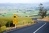 Scenic winding road with road sign in New Zealand
