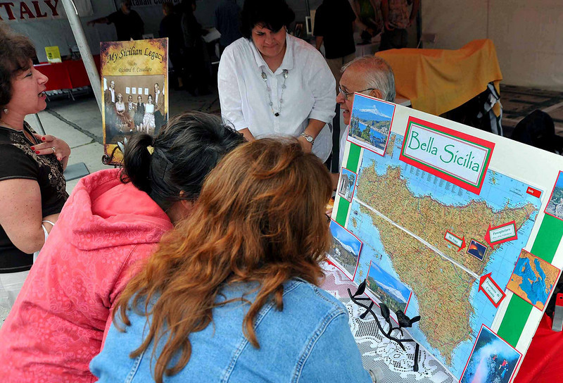 Visitors studying map of Sicily to learn where their families originated