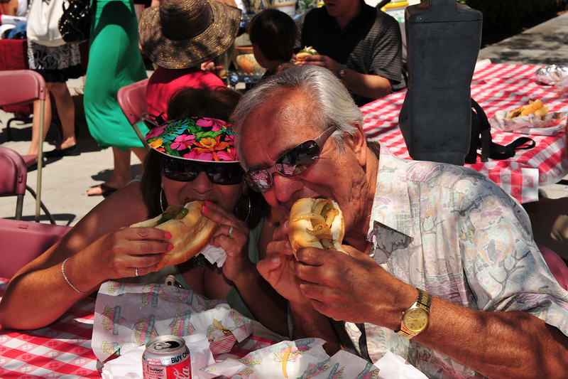 Festival visitors dig into a Sicilian sausage sandwich