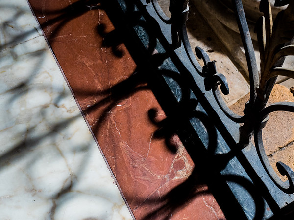 Iron fencing and shadow inside Duomo di Catania