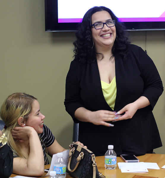 Lynn, Ma. 6-7-17. Yohanna Chalas, left, watches fellow employee Odalis Rodrigues, right, give her short presentation in English during the student recognition ceremony for those employees who finished the workplace based English classes at Sidekim Foods in Lynn.