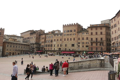 """Piazza del Campo in Siena, the main square, commonly called """"il Campo"""" was built on the intersection of the three main roads that lead to and from Siena, destined to be a neutral ground where political and civic holidays could be celebrated. The homogenous architectural form of the square and the buildings facing it was not an accidental happening; the government created guidelines in 1297, before the actual building of the square and civic buildings.  from:  http://www.discovertuscany.com"""