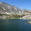 """Cooney Lake.  In the back, right, are the """"red bumps"""" that one must go over or around to get on top of the talus slope up that leads to the summit"""