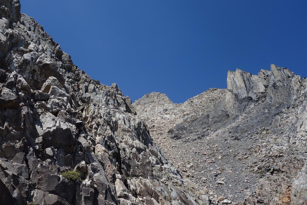 The ramp below the red rock took us to the narrow chute.  The striated rock on right was familiar from other photos we had seen.  The outcropping in middle is not summit, but close.  Summit is behind it.  The ramp ends at the chute at N37 33.700 W118 51.333