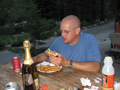 Rafael enjoying an afterhike burger - note the bottle of champagne we hauled up the mountain.