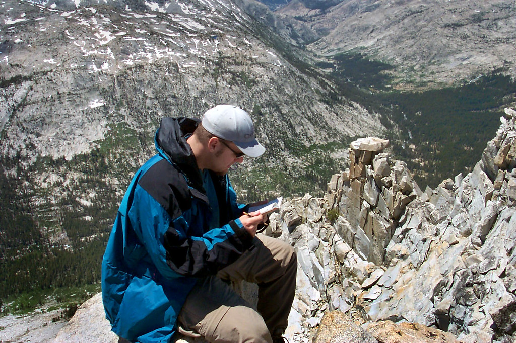 Andy looking through the summit register. It's a long way down to Piute Canyon.