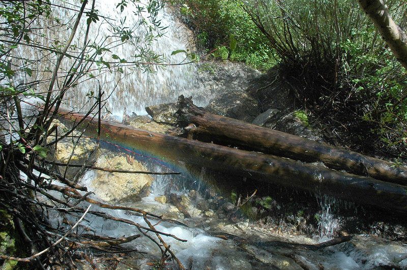 This waterfall is dumping on the trail, cool little rainbow on the left.