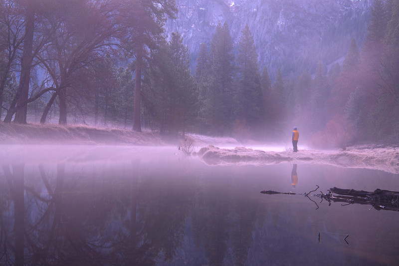 JP takes in the view while standing along the banks of the Merced River during a misty sunrise in Yosemite Valley.