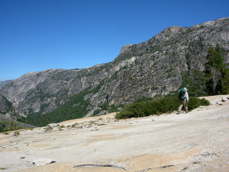 Dave crosses the granite<br /> <br /> This trail alternated between exposed granite, meadow walking, and pine forests