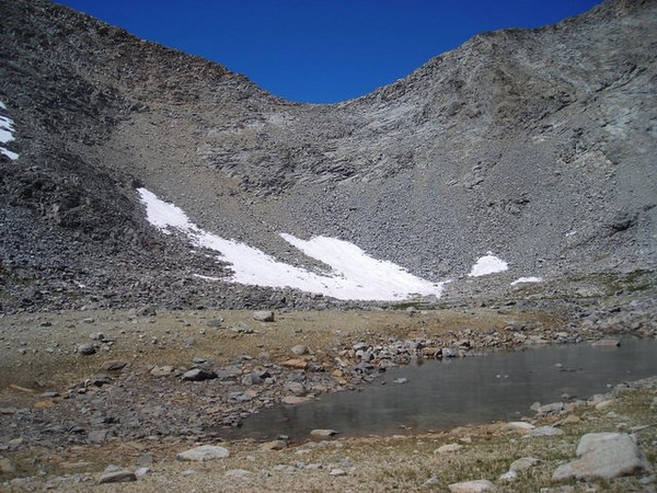 Climbing to Mather Pass<br /> <br /> The trail switchbacks above the snow field, to the left of the pass, but first we have to climb toward the right of the pass and take a long switchback across the face.