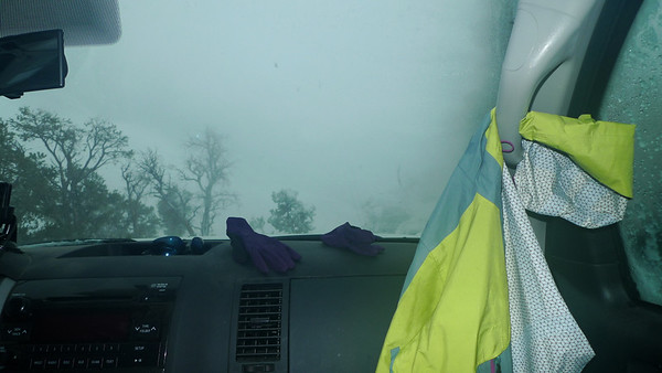 """...here I am at 7 am, sitting in the front of the truck trying to get warm and dry out. We slept under the lid of the truck but it didn't fasten all the way. The wind blew snow in and I woke up at 5 am in a saturated wet down sleeping bag, surrounded by about six inches of snow. I was actually wet INSIDE my sleeping bag due to melting snow underneath me. D and I made a run for it to the front seat of the truck as the snow flew horizontally and the wind blew around us. Over the next two hours we would make mad dashes to retrieve our gear, pack up the truck, and coordinate with the group in between breaks inside the cab to warm up and dry out. The snow was drifted nearly 3 feet in front of the truck and I was worried about the road conditions. We had plenty of supplies to stay put for a few days but my sleeping bag needed warm and dry air.  Luckily, the road was okay, and the Tundra and other vehicles handled the 6-8"""" of fresh powder with no trouble."""
