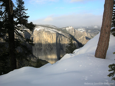 Sun starts to hit El Cap while the high country remains shrouded in clouds