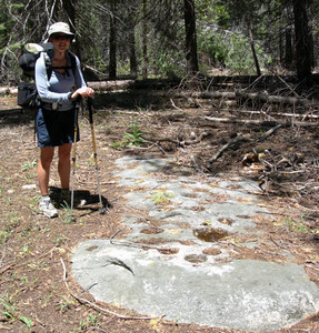 Pausing by one of the best example of Native American mortars, on a rock that spans the trail