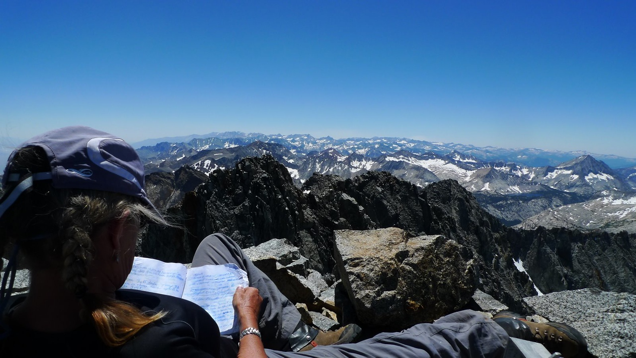 reading the summit register and enjoying a summit. Smoke on the horizon from a fire in the Kern drainage.