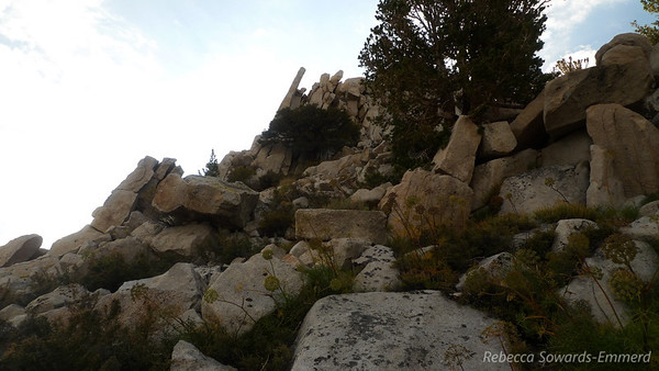 Heading up through some talus, looking towards the summit block.