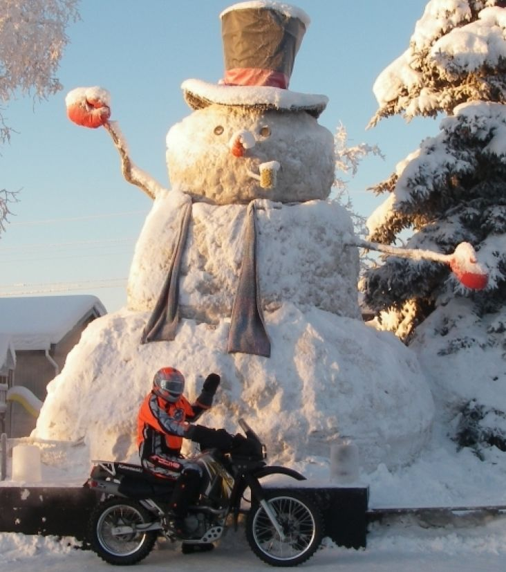 """In Anchorage, on one of the side streets, someone builds this gigantic snowman every year.  It is nicknamed """"Snowzilla"""".  That's my friend Mark Haldane on his KLR in front of it."""