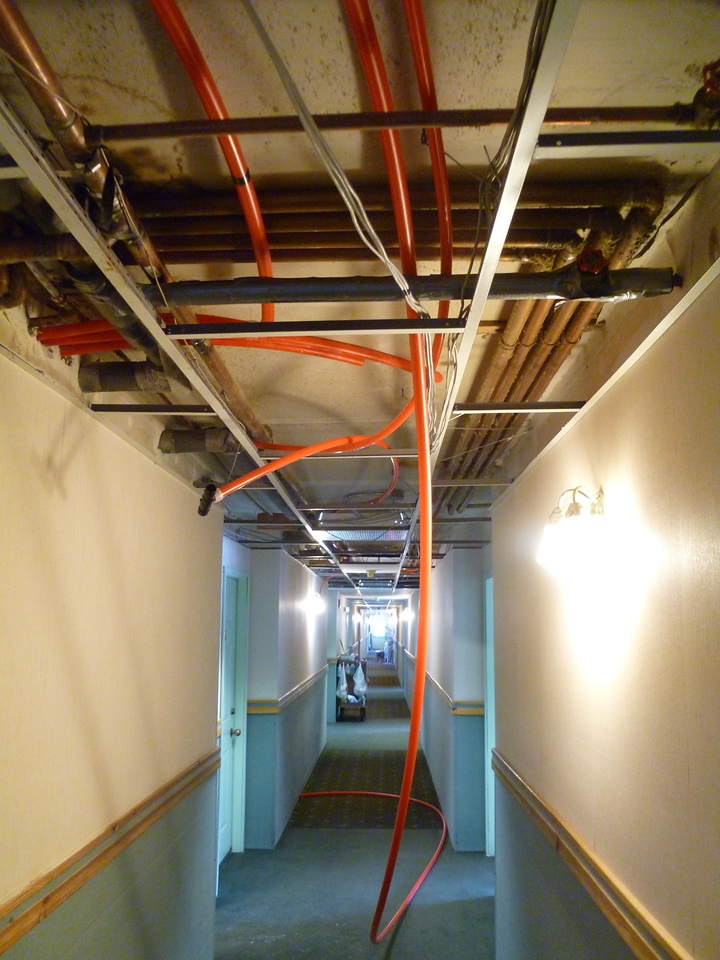 This photo was taken right outside the boiler room, with the four pex lines coming through the wall on the upper left, then going in their different directions to convey hot water to the rooms.