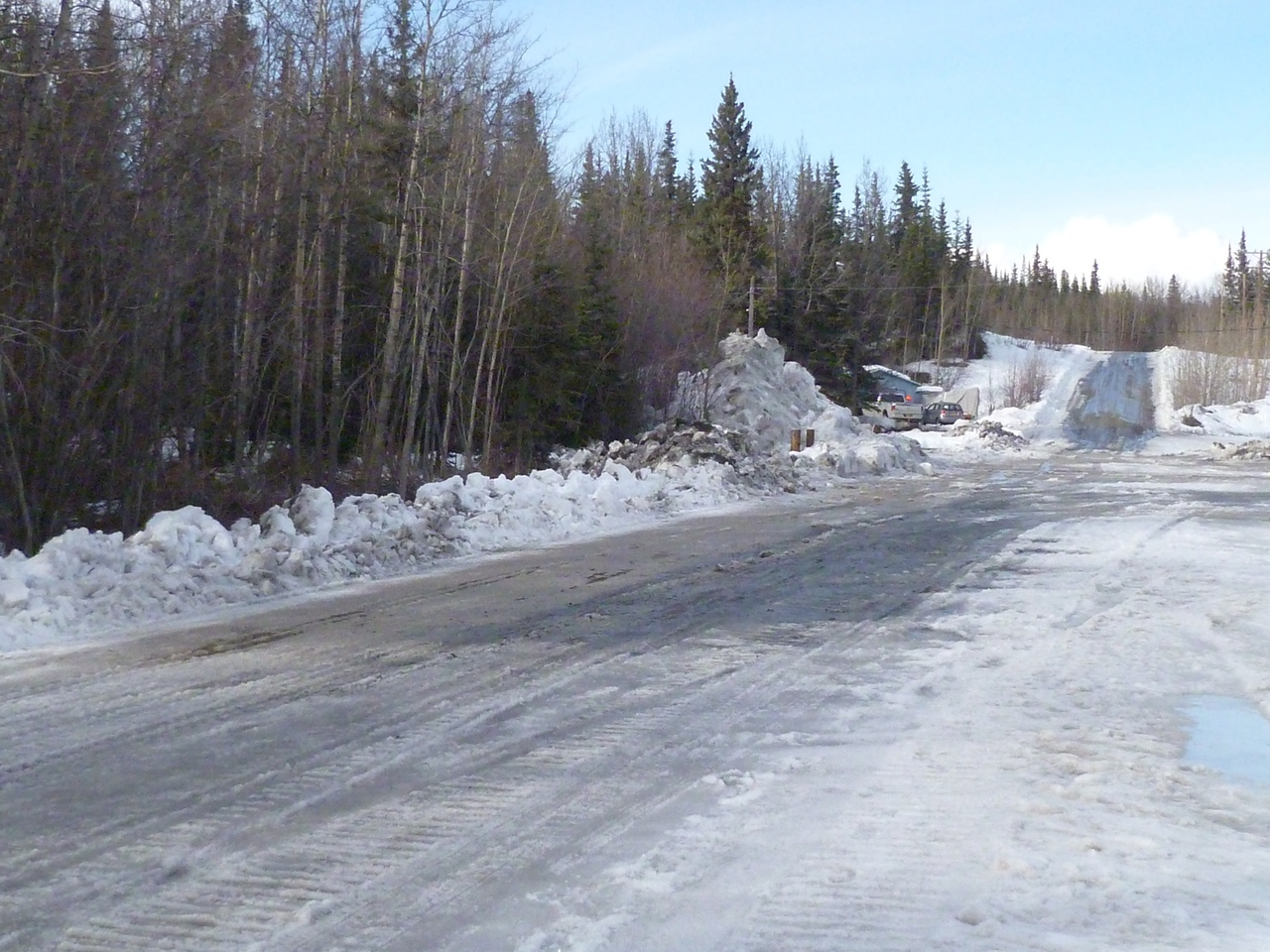 One of the side streets in Glennallen, where a bulldozer has been used to scrape away the softened snowpack and pile it to the side, where it will melt and soon create streams crossing the road.