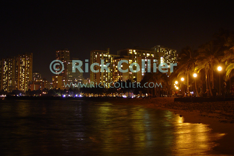 The public beach near Kapiolani Park is illuminated by streetlights, with the lights of Waikiki and Honolulu in the background.  Oahu, Hawaii.<br /> <br /> <br /> <br /> <br /> <br /> <br /> Hawaii Hawai'i Honolulu Waikiki beach night lights reflection new year fireworks