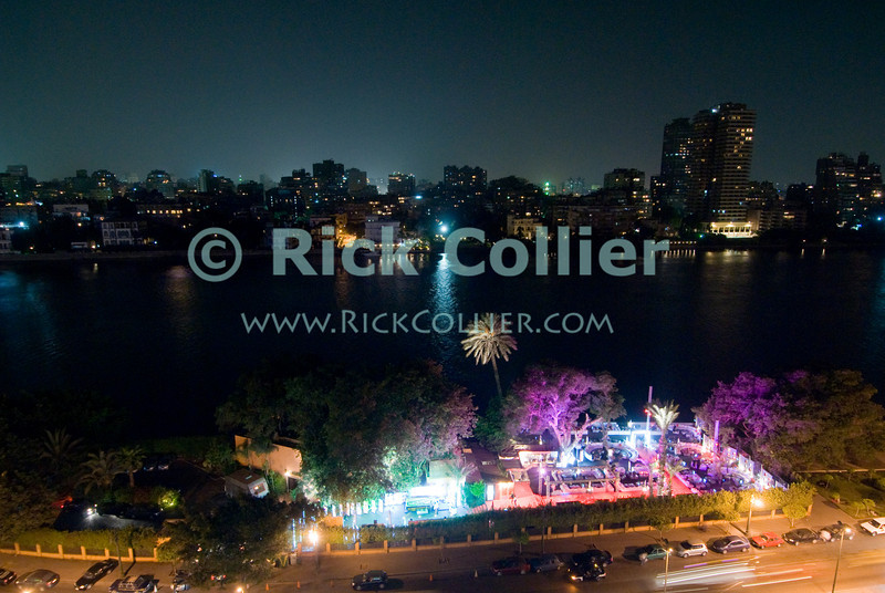 """Cairo, Egypt -- An open-air restaurant and the """"Corniche du Nile"""" street light the eastern shore of the Nile at night.  Looking west across the Nile from a balcony at the Conrad Hotel. © Rick Collier / RickCollier.com.<br /> <br /> <br /> <br /> <br /> <br /> travel; vacation; tour; tourism; tourist; destination; Egypt; Cairo; river; Nile; """"Nile River""""; restaurant; city; cityscape; skyline; view;"""