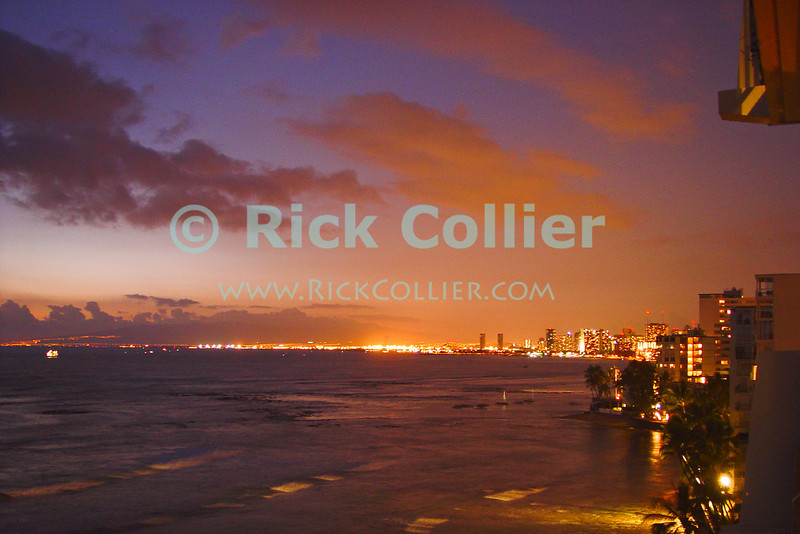The lights of Honolulu and Waikiki light up the bay as the sunset light fails at dusk.  Waikiki, Honolulu, Oahu, Hawaii.  © Rick Collier<br /> <br /> <br /> <br /> <br /> <br /> <br /> <br /> Hawaii Hawai'i Oahu Honolulu Waikiki beach bay sail boats sailboat sailboats city skyline seashore evening sun set sunset night evening lights city lights dusk