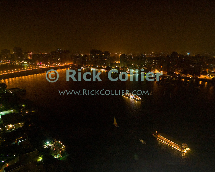 The lights of downtown Cairo and passing boats illuminate the nile river at night.  © Rick Collier<br /> <br /> <br /> <br /> <br /> <br /> <br /> Egypt Cairo lights boat boats 'after dark' night Nile river