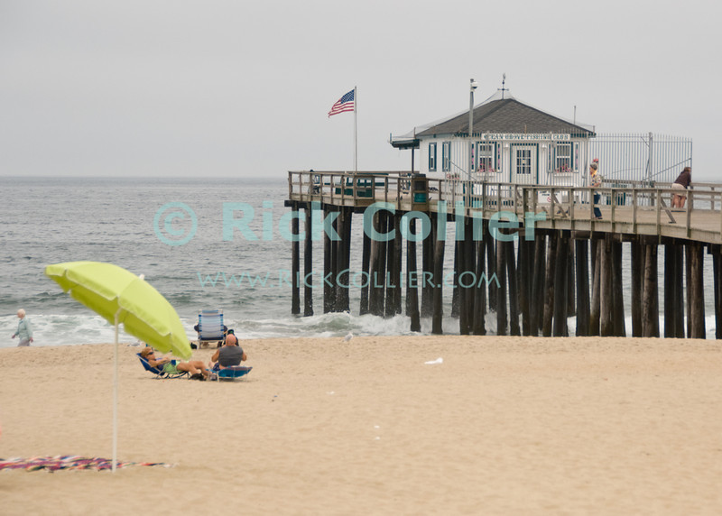 """""""Fishing Club"""" - The Ocean Grove fishing club sits on a private pier overlooking the public beach.  Ocean Grove, New Jersey, USA.<br /> <br /> <br /> USA """"New Jersey"""" NJ """"Ocean Grove"""" Ocean Grove flag pier dock fishing club public beach umbrella"""