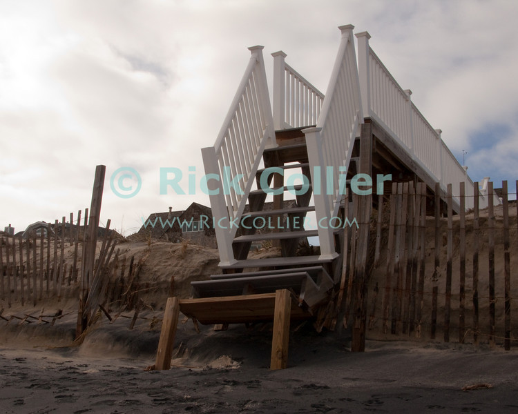 Broken stairs to the beach at Bethany, Delaware, now traverse a new sand cliff face rather than the dune that was removed by the November 2009 nor'easter.