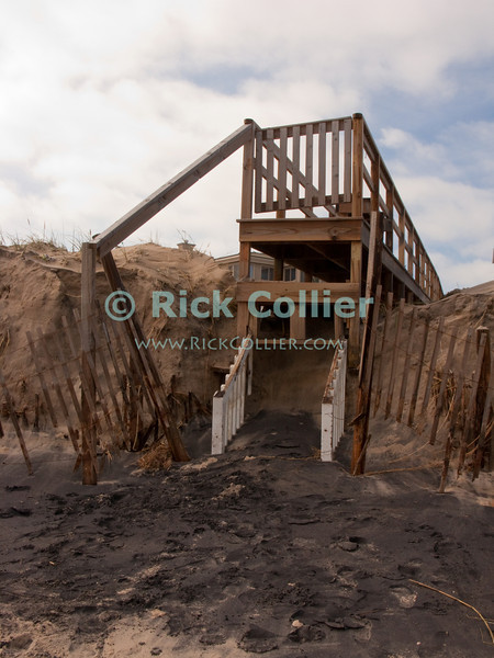 A wooden walkway now ends ten feet above the level of Bethany Beach, Delaware, after the steps and dune were removed by a nor'easter in November 2009.