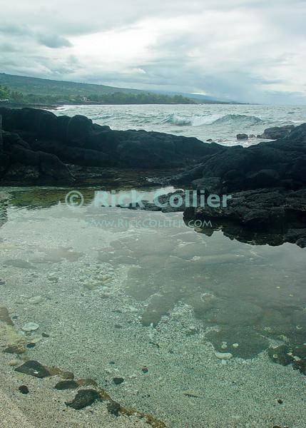 A tidal pool invites wading just feet from the breaking surf.  Kona, the Big Island, Hawaii.<br /> <br /> <br /> <br /> <br /> <br /> <br /> Hawaii Hawai'i Kona big island beach sea ocean tidal pool wade wading surf