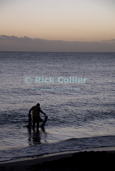 St. Eustatius (Statia) - Local families go to the small beach in Lowertown on Statia in the late evening.  These two small kids were so excited that dad had to take them both into the water at the same time.   © Rick Collier