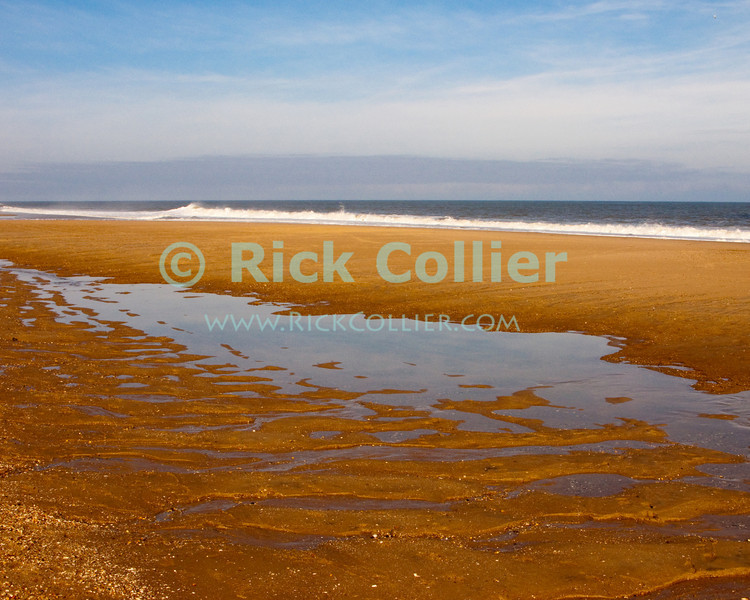 New tidal pools reflect the sky in the first clear hours after a nor'easter widened the beach at Bethany, Delaware, in November 2009.