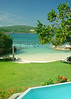 "Amanoka Villa, Discovery Bay, Saint Ann Parish, Jamaica.  Every day in tropical paradise, guests are hard-pressed to choose between the beautiful beach, the manicured lawn, or the ""infinity"" pool.  © Rick Collier<br /> <br /> <br /> <br /> <br /> <br /> Jamaica Discovery Bay Dry Harbor Bay Amanoka Villa tropical island paradise swimming pool beach relaxation shower ocean blue green water palm sea grape tree shade lawn grass flower garden white sand beach"