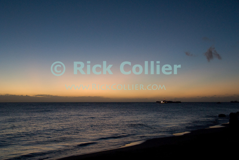 St. Eustatius (Statia) - Scenic view out into the Caribbean sea from the beach at sunset.  Moored oil tankers are visible under a colorful sunset.  © Rick Collier