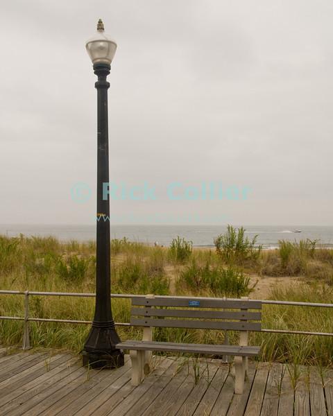 """Ocean View"" - The boardwalk in Ocean Grove, New Jersey, USA, is mostly deserted in wintertime.<br /> <br /> <br /> USA ""New Jersey"" NJ ""Ocean Grove"" Ocean Grove Ocean Avenue beach boardwalk streetlight bench seat railing dune dunes sea Atlantic Ocean"