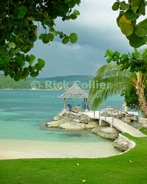 Amanoka Villa, Discovery Bay, Saint Ann Parish, Jamaica.  Looking across the manicured lawn, guests enjoy a fantasice tropical view of beach, walk, gazebo, and the beautiful blue-green water from the main house at Amanoka.  © Rick Collier<br /> <br /> <br /> <br /> <br /> <br /> Jamaica Discovery Bay Dry Harbor Bay Amanoka Villa tropical island paradise swimming beach relaxation gazebo walk ocean blue green water palm sea grape tree shade lawn grass white sand beach